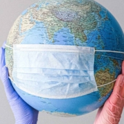 A globe of the world sporting a surgical mask held up by a pair of hands in purple and orange surgical gloves.