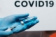 Close shot of a vaccine being drawn from a vial into a syringe. The word COVID-19 floats in the background.